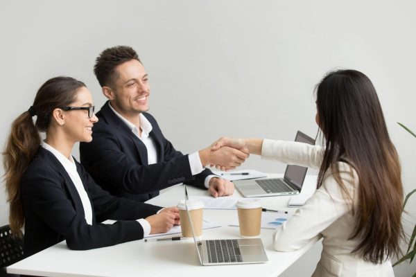 Friendly satisfied partners handshaking at group meeting thanking for successful teamwork, smiling millennial businessman shaking hand greeting businesswoman, respect or making contract deal concept